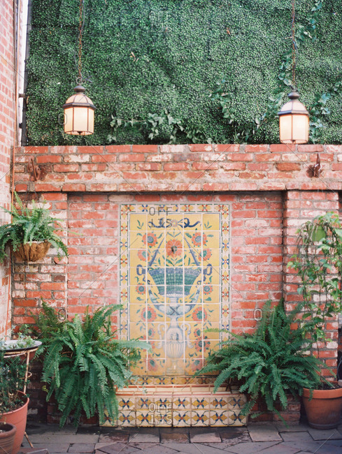 Brick wall with a mosaic tile fountain in a garden