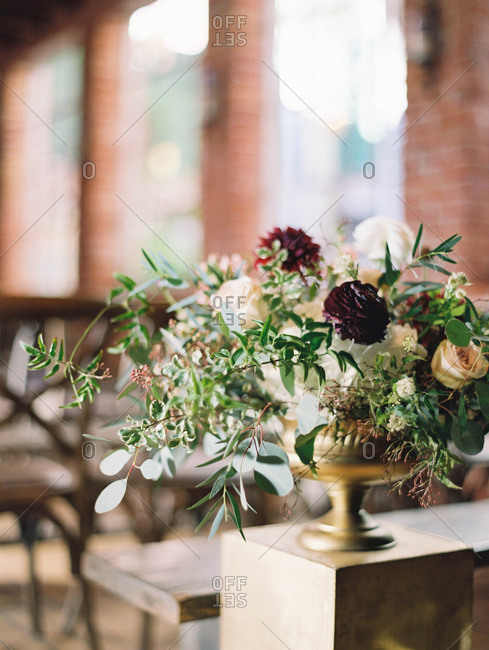 Floral arrangement with pink, green and dark red flowers in a brass urn on a pedestal