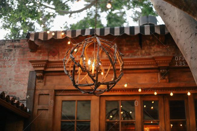 Outdoor lantern made from sticks hanging near an elegant doorway