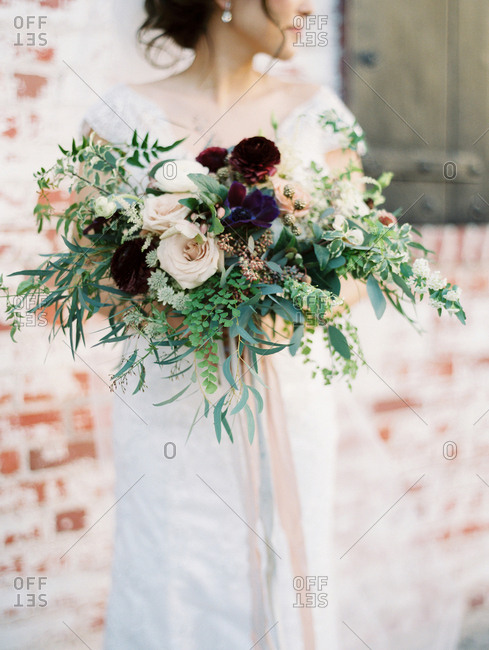 Bride holding a large bouquet in front of a brick building