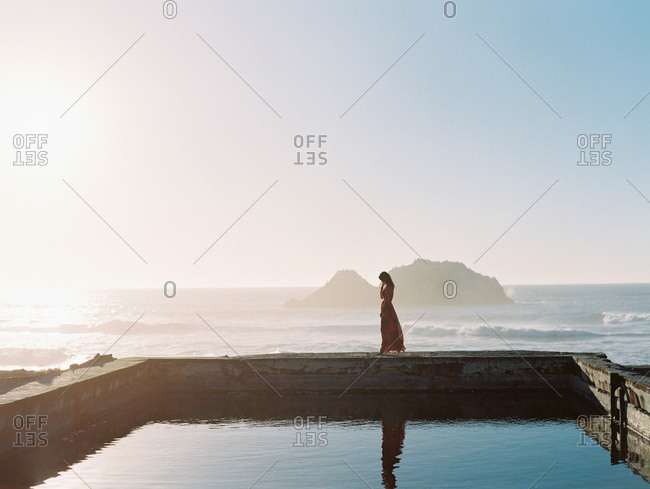 Woman walking on a wall near the sea at sunset