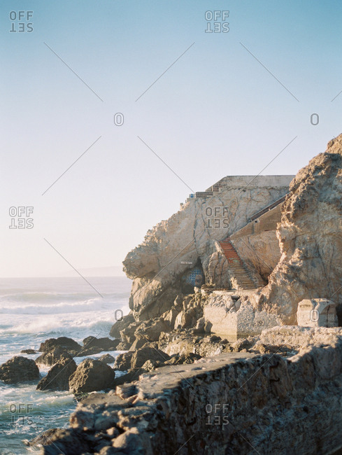 Stairs on the side of a rocky coast at sunset