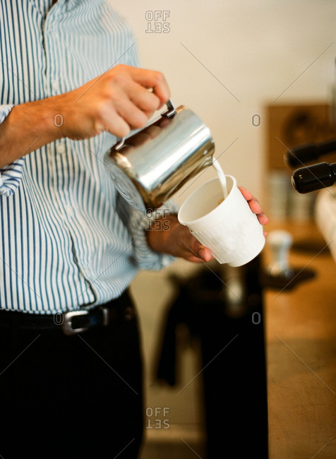Man pouring cream into a paper coffee cup