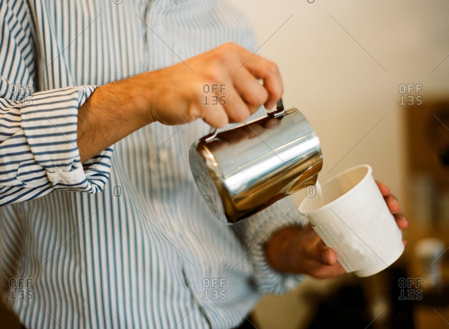 Hands of a man pouring creamer into a paper coffee cup