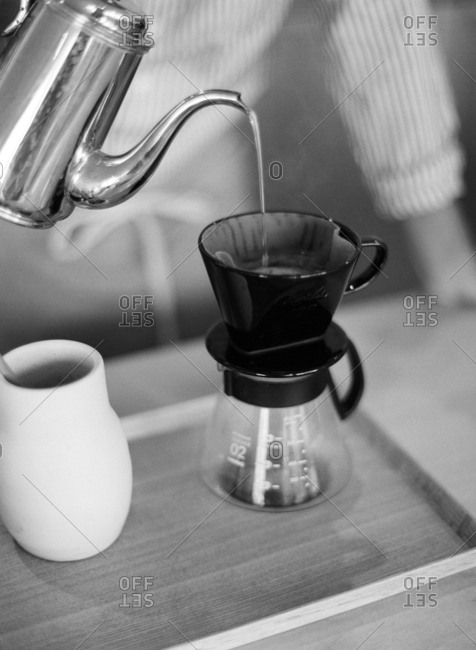 Barista pouring water into a pour-over coffee maker