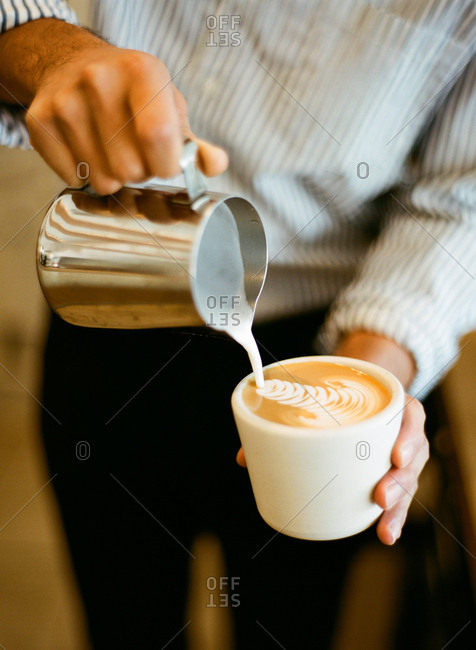 Man adding cream to the top of a cappuccino beverage