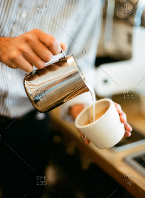 Man pouring cream into a coffee beverage