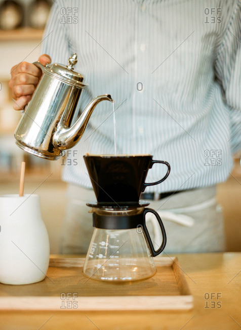 Man pouring hot water into a pour-over coffee maker