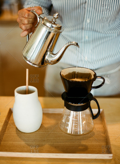 Man pouring hot water over coffee in a pour-over carafe