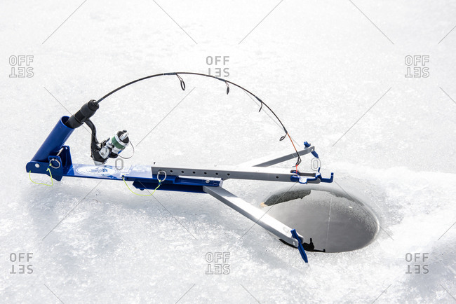 August 10, 2015: Ice fishing tilt with pole set over hole in frozen lake
