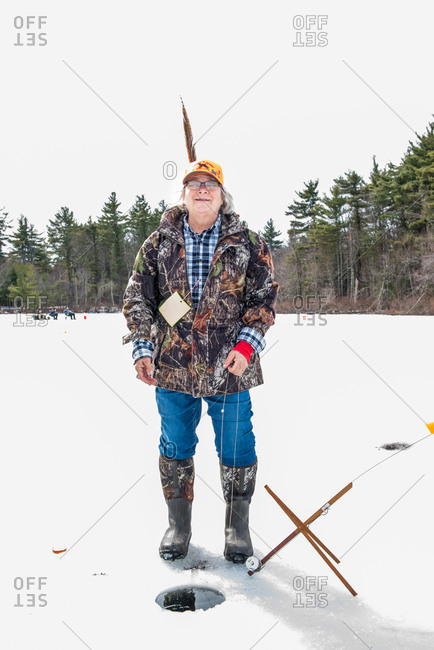 August 10, 2015: Smiling woman with turkey feather in cap ice fishing on frozen lake