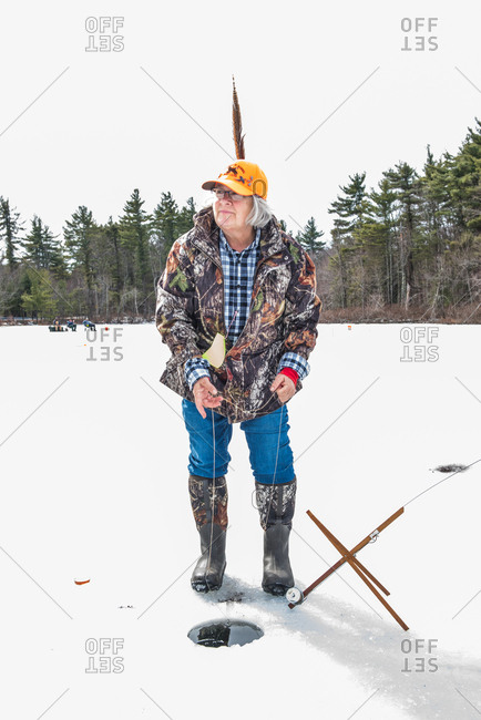 August 10, 2015: Woman with turkey feather in cap ice fishing on frozen lake