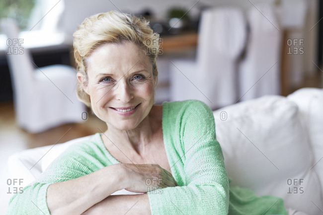 Portrait of smiling mature woman on armchair