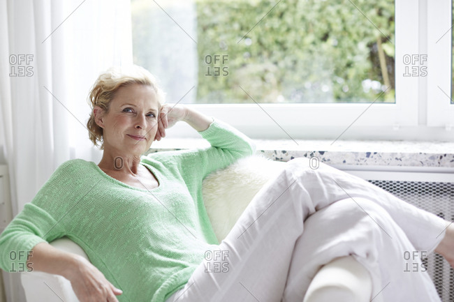 Smiling mature woman on armchair
