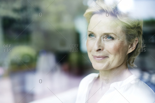 Portrait of smiling mature woman behind a window