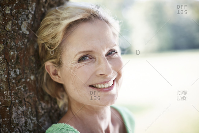 Portrait of smiling mature woman at a tree