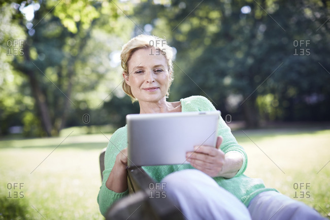 Mature woman using digital tablet on park bench