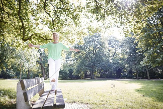 Mature woman balancing on park bench