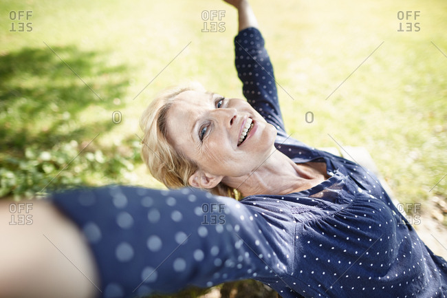 Happy mature woman stretching outdoors