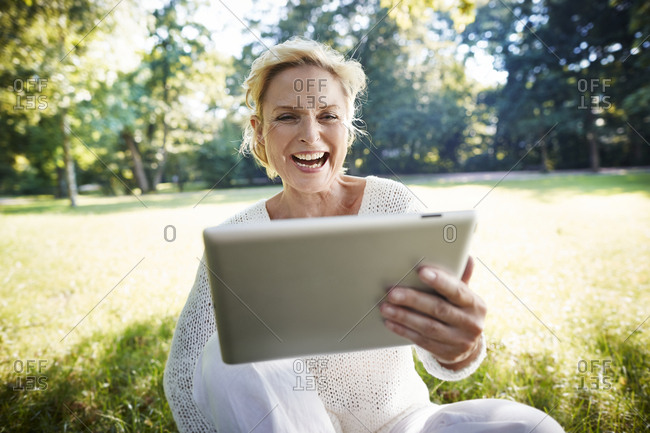 Laughing mature woman holding digital tablet in park