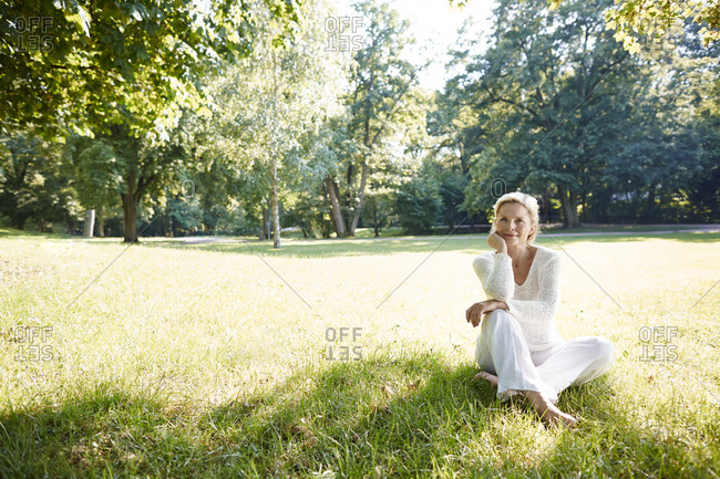 Smiling mature woman sitting on meadow in park