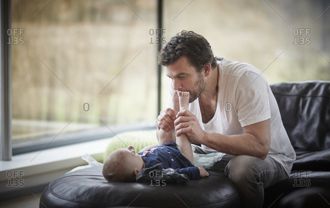 Father changing diaper of his baby in living room