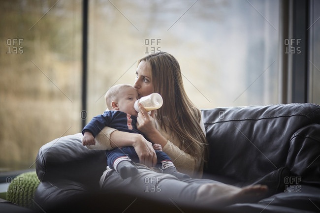 Mother bottle feeding baby on couch