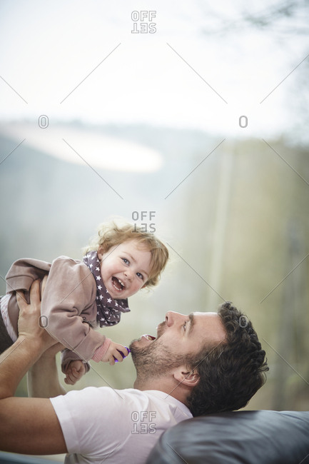 Happy father playing with daughter at home