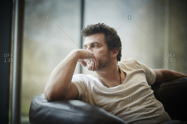 Pensive man sitting on couch