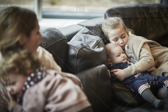 Girl and baby on couch with mother and daughter in foreground