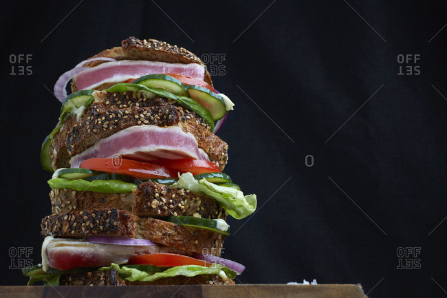 Fresh Tuna Steak Sandwich stacked with lettuce, tomato and cucumbers on seeded artisan bread