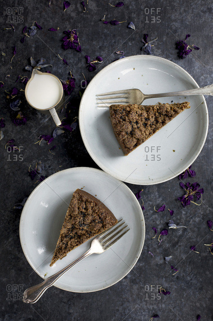 Two slices of Black Sesame Crumb Cake served with cream. Photographed on black/grey background.