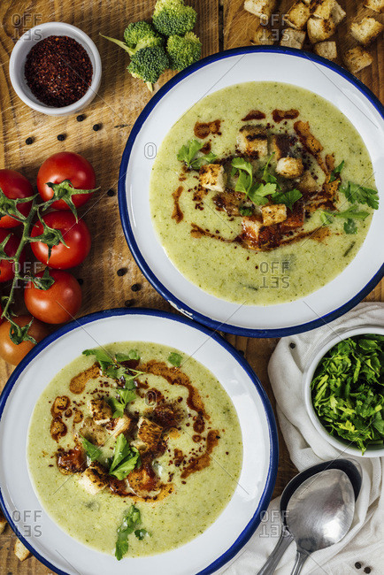 Cream of broccoli soup in two white bowls, garnished with a chili powder sauce, croutons and parsley
