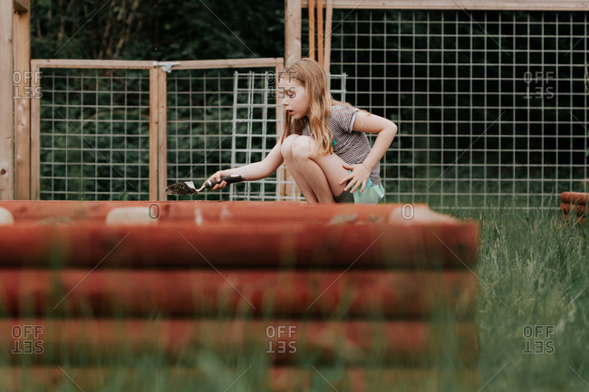 Young girl digging in raised bed of garden