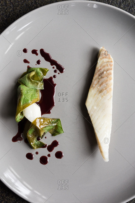 Minimalist plating of fish and vegetable with soy sauce