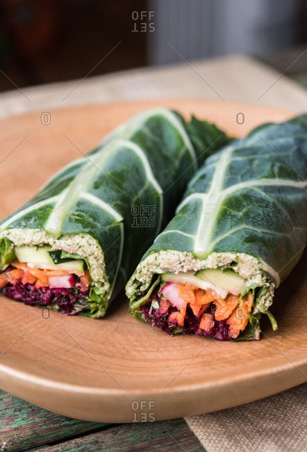 Two vegetable salad wraps on wooden board