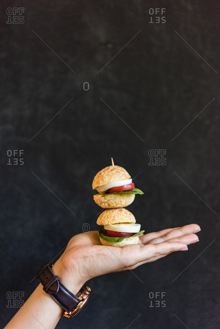 Hand holding two miniature sandwiches