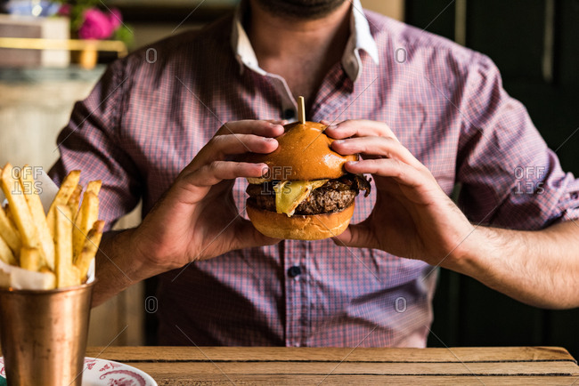 Man in plaid shirt holding a burger