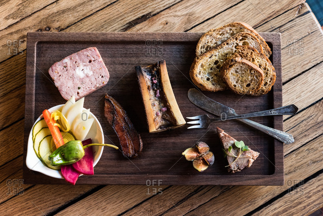 Charcuterie with vegetables and bread on wooden board