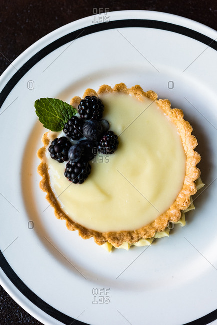 Overhead view of a lemon curd tart with blackberries