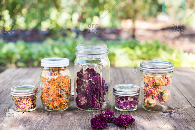 Jars of dried flowers on outdoor wooden table