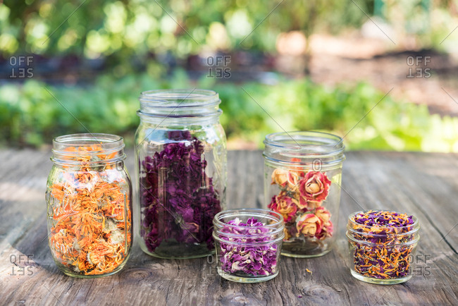 Edible flowers in jars on wooden table outdoors