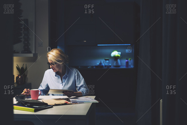 Businesswoman using technologies while sitting at desk in home office