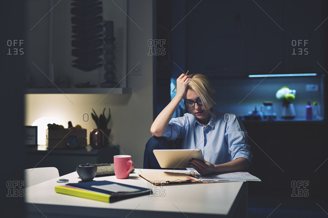 Businesswoman with head in hand using tablet computer at desk in home office