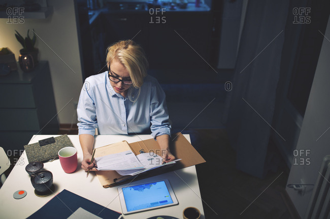 High angle view of businesswoman reading documents while sitting at desk in home office