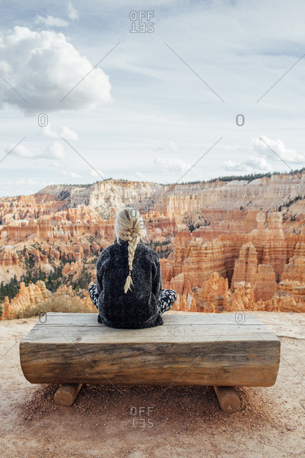 Rear view of woman sitting on bench against rock formations at Bryce Canyon National Park
