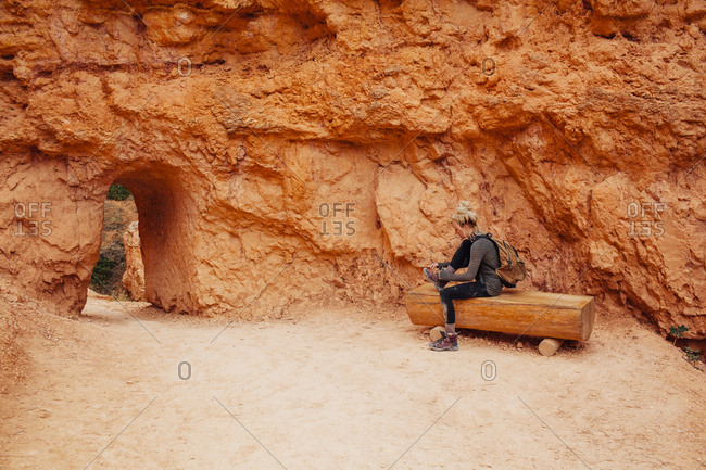 Woman tying shoe lace while sitting on bench at Bryce Canyon National Park