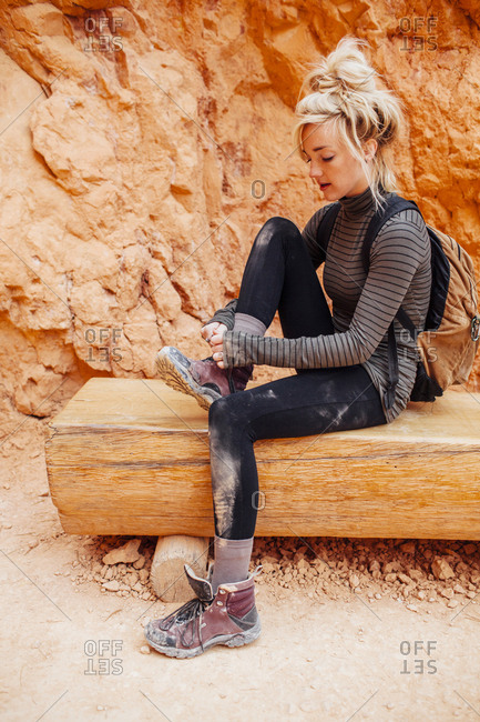 Woman tying shoe lace while sitting on bench against rock formations
