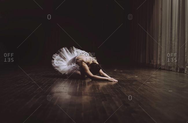 Ballet dancer practicing while sitting on floor in room