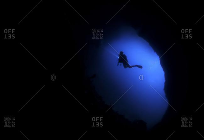 Person scuba diving in cave undersea